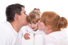 Счастливая семья: родители целуя дочь изолированную на белом backgro Стоковые Фото