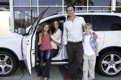 Счастливая семья рядом с белым автомобилем Стоковые Фотографии RF