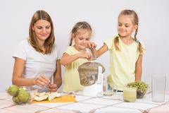 Счастливая семья сжимает сок в juicer Стоковые Фото