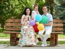 Счастливая семья сидит на деревянной скамье в парке города, сезоне лета, ребенке и родителе, группе в составе 4 люд Стоковое Изображение RF