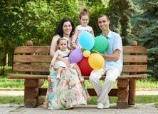 Счастливая семья сидит на деревянной скамье в парке города, сезоне лета, ребенке и родителе, группе в составе 4 люд Стоковое фото RF