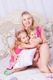 Счастливая семья сидит на кровати Стоковое Изображение RF