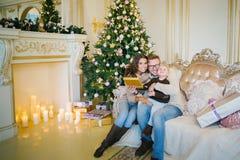 Счастливая семья сидя на софе около рождественской елки и камина Стоковые Фотографии RF