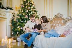 Счастливая семья сидя на софе около рождественской елки Стоковые Фото