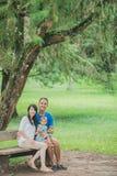 Счастливая семья сидя на стенде в парке стоковое фото