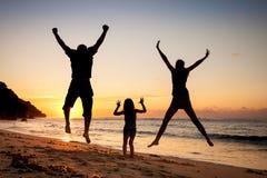 Счастливая семья скача на пляж стоковые изображения rf