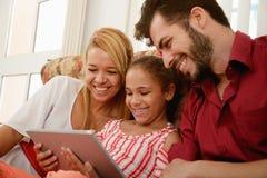 Счастливая семья смеясь над смотрящ видео на планшете Стоковое Фото