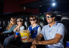 Счастливая семья смотря кино 3D в театре Стоковые Фото