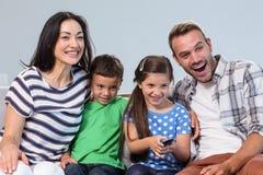Счастливая семья смотря телевидение с их 2 детьми Стоковая Фотография RF