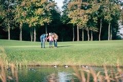 Счастливая семья смотря уток в парке Стоковое фото RF