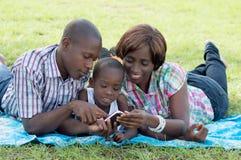 Счастливая семья советуя с мобильным телефоном стоковые фото
