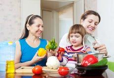 Счастливая семья совместно варя вегетарианский обед Стоковые Изображения RF