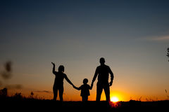 Счастливая семья стоя в парке на времени захода солнца Концепция дружелюбной семьи стоковое изображение