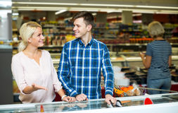 Счастливая семья стоя около дисплея с замороженными продуктами Стоковое фото RF
