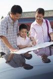 Счастливая семья стоя рядом с автомобилем и смотря вниз на карте Стоковое Изображение RF