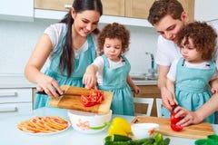 Счастливая семья с двойными дочерьми в кухне Жизнерадостная мать Стоковое Фото