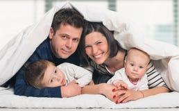 Счастливая семья с дет в кровати Стоковое Изображение