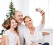 Счастливая семья с камерой дома Стоковое фото RF