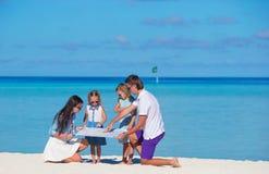 Счастливая семья с картой на пляже Стоковые Фото