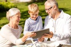 Счастливая семья с ПК таблетки outdoors Стоковые Фото