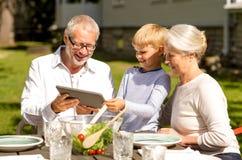 Счастливая семья с ПК таблетки outdoors Стоковое Изображение RF