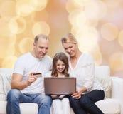 Счастливая семья с портативным компьютером и кредитной карточкой Стоковое фото RF
