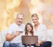 Счастливая семья с портативным компьютером и кредитной карточкой Стоковая Фотография RF
