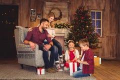 Счастливая семья с подарками на рождество стоковое фото rf