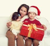 Счастливая семья с подарком коробки, женщина с ребенком в шляпе хелпера santa - концепции праздника рождества Стоковое Изображение RF