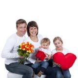 Счастливая семья с сердцем, подарочной коробкой и цветками стоковая фотография