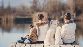 Счастливая семья с любимчиками около озера Стоковое фото RF