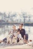 Счастливая семья с любимчиками около озера Стоковая Фотография RF