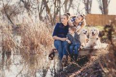 Счастливая семья с любимчиками около озера Стоковое Изображение