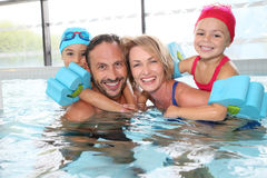 Счастливая семья тратя полезного время работы в бассейне Стоковое Изображение RF