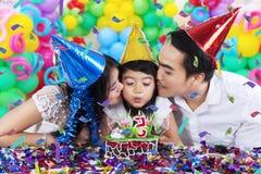 Счастливая семья дуя свеча дня рождения Стоковые Фотографии RF