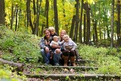 Счастливая семья 5 человек сидя в лесе осени Стоковые Изображения RF