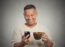 Счастливая середина постарела хорошие новости чтения человека на кофе выпивая чашки smartphone Стоковая Фотография RF