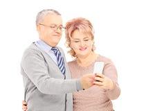 Счастливая середина постарела человек и женщина смотря мобильный телефон Стоковые Фото