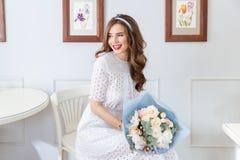 Счастливая симпатичная женщина с букетом цветков сидя в кафе стоковые изображения rf