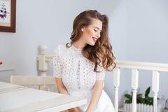 Счастливая симпатичная молодая женщина в белом платье сидя на кафе стоковые фотографии rf