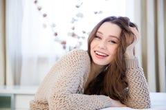 Счастливая симпатичная расслабленная молодая женщина сидя дома стоковая фотография rf