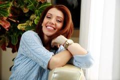 Счастливая склонность женщины на софе Стоковые Фото