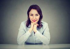 Счастливая склонность женщины на таблице усмехаясь на камере стоковое фото rf