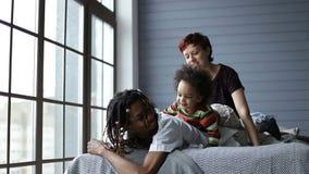 Счастливая смешанная семья играя с сыном в спальне сток-видео