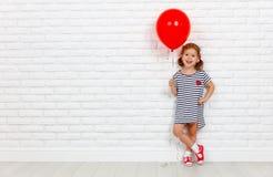 Счастливая смешная девушка ребенка с красным шариком около кирпичной стены Стоковое Изображение RF