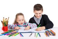 Счастливая смешная притяжка детей Мальчик и девушка рисуют карандаши lego руки творческих способностей принципиальной схемы здани Стоковое Фото