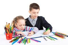 Счастливая смешная притяжка детей Мальчик и девушка рисуют карандаши lego руки творческих способностей принципиальной схемы здани Стоковые Изображения