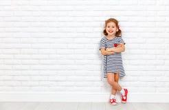 Счастливая смеясь над девушка ребенка около стены кирпича пустой Стоковые Фото