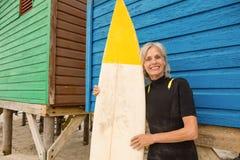 Счастливая старшая женщина держа surfboard пока готовящ голубую деревянную хату Стоковые Изображения RF