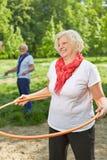 Счастливая старшая женщина делая спорт с обручем Стоковое Изображение
